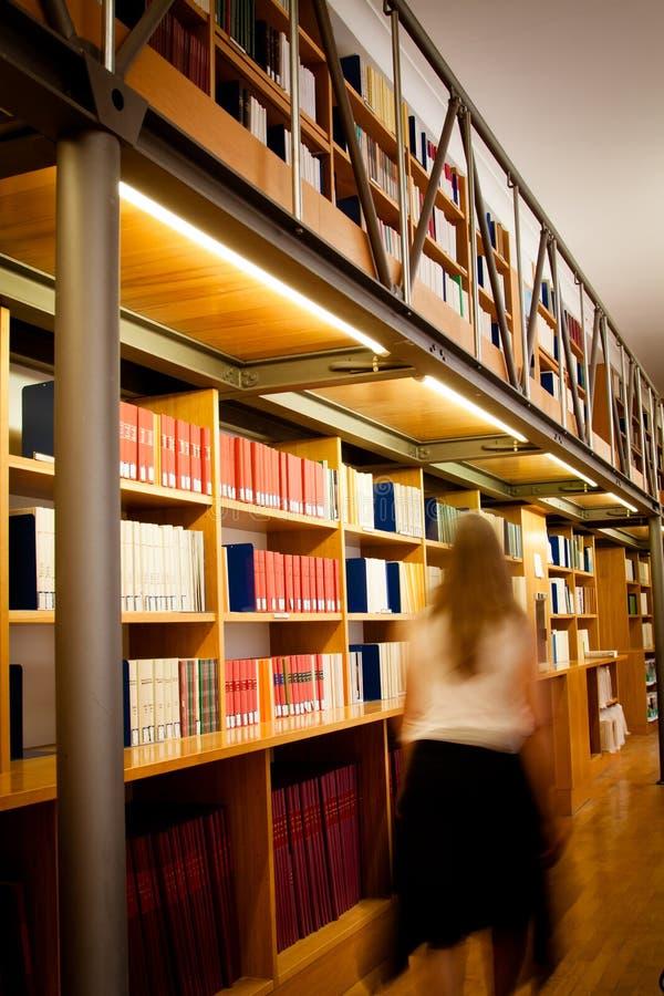 Bibliotecario che cammina giù una navata laterale delle biblioteche immagini stock