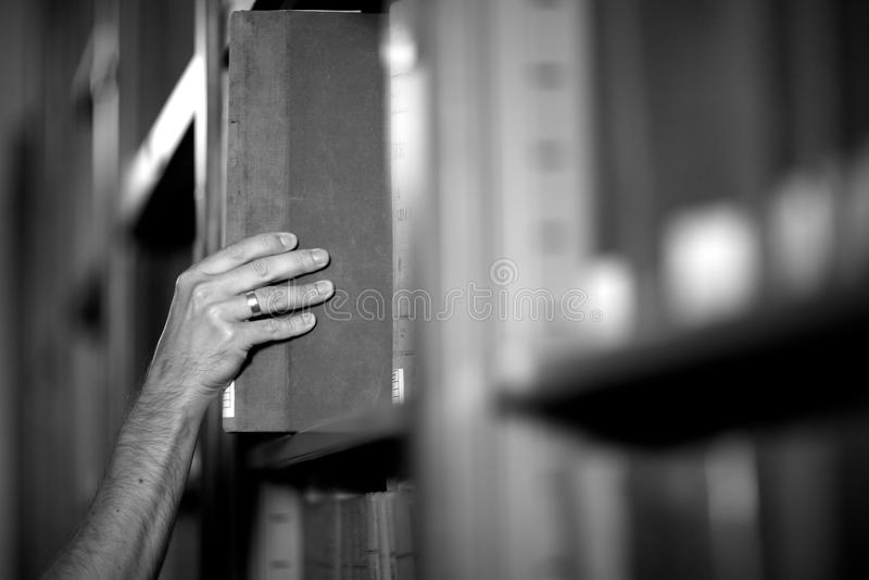 bibliotecario che prende un libro da immagini stock