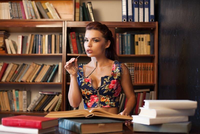 Bibliotecario de la mujer en los vidrios que se sientan en el libro que estudia de la tabla fotos de archivo libres de regalías