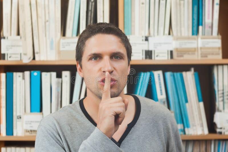 Bibliotecario de sexo masculino moreno que pide silencio en biblioteca imagen de archivo