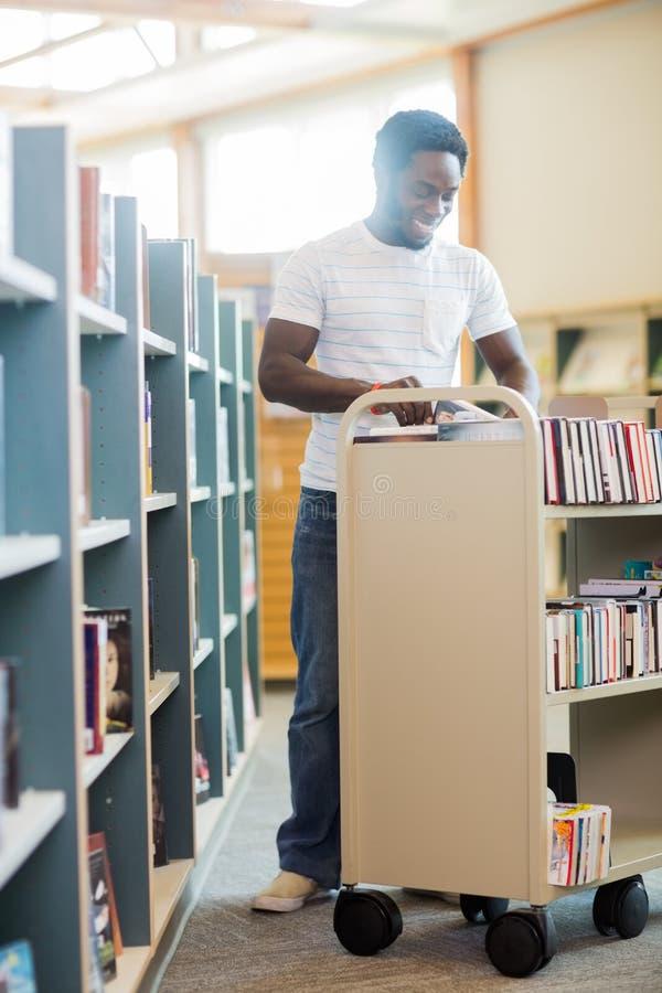 Bibliotekarien With Trolley Of bokar arbete i arkiv arkivbild