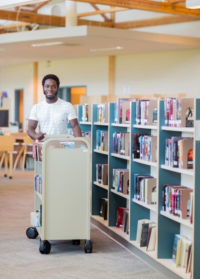 BibliotekarieWith Trolley Of böcker i bokhandel fotografering för bildbyråer