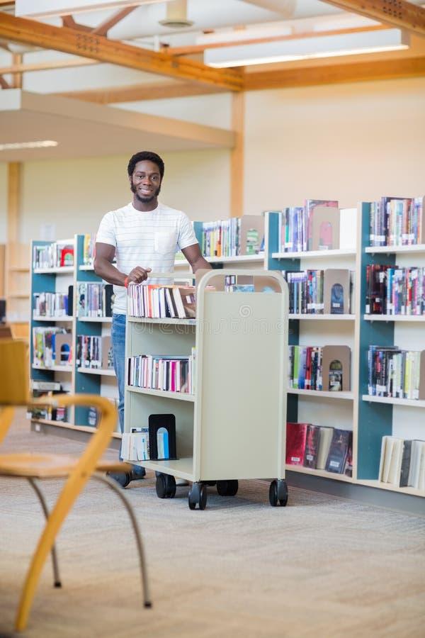 BibliotekarieWith Trolley Of böcker som in ler royaltyfria foton