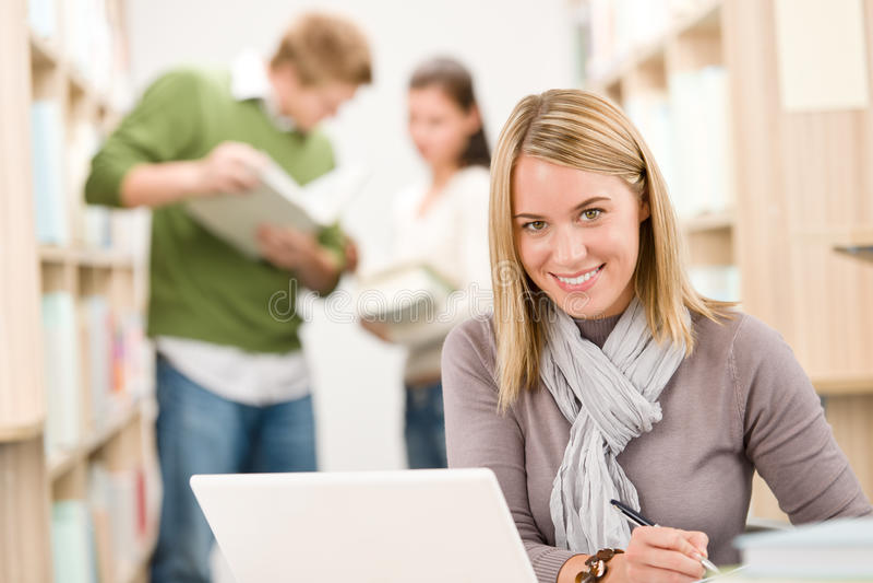 Bibliothèque de lycée - étudiant heureux avec l'ordinateur portatif image libre de droits