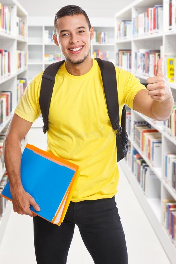 Bibliothèque réussie de succès de jeune homme d'étudiant apprenant des pouces de format de portrait vers le haut des personnes de images libres de droits