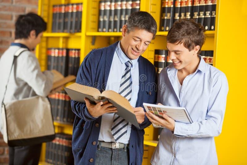 Bibliothèque universitaire d'Assisting Student In de bibliothécaire photos libres de droits