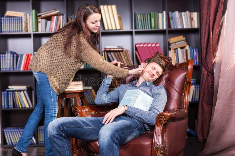 Bibliothécaire réveillant un homme de sommeil dans la bibliothèque image stock