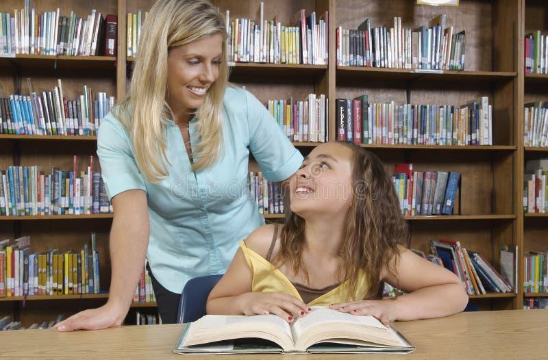 Bibliothecaris And Student Looking bij elkaar stock afbeeldingen