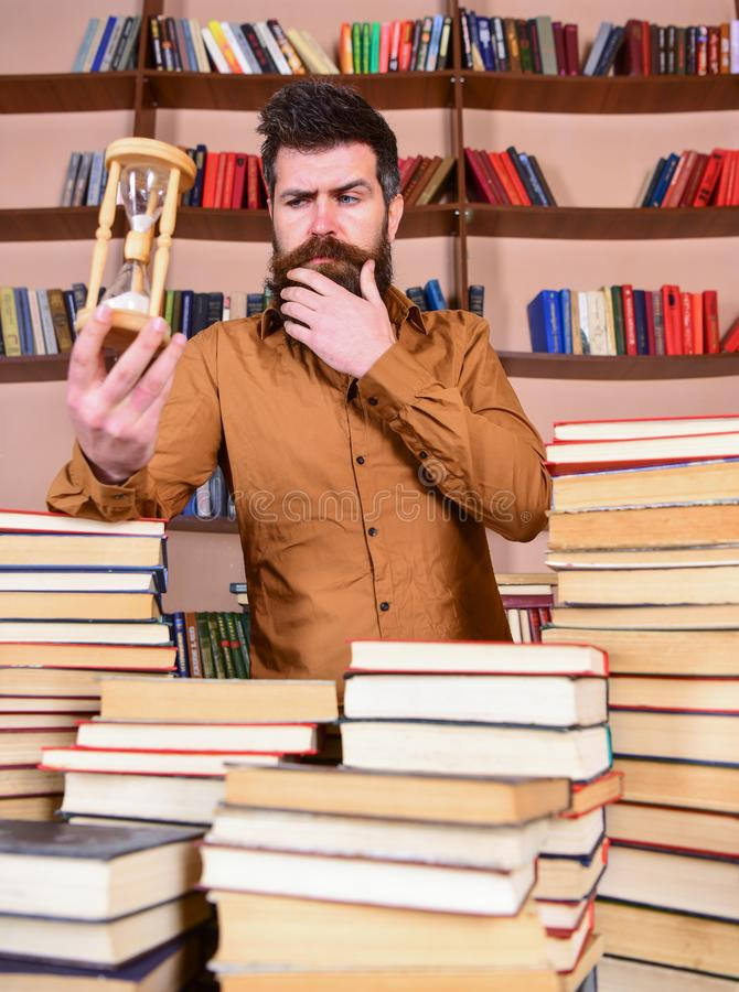 Bibliothecarisconcept De mens op nadenkend gezicht bevindt zich tussen stapels van boeken, terwijl zandloper, boekenrekken houdt stock afbeelding
