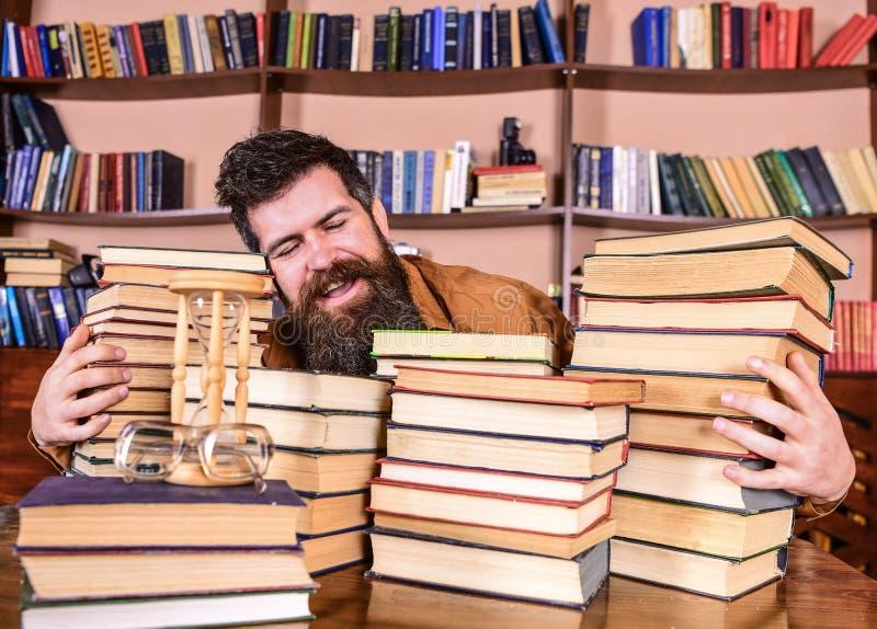 Bibliothecarisconcept Mens op gelukkig gezicht tussen stapels van boeken, terwijl het bestuderen in bibliotheek, boekenrekken op  royalty-vrije stock fotografie