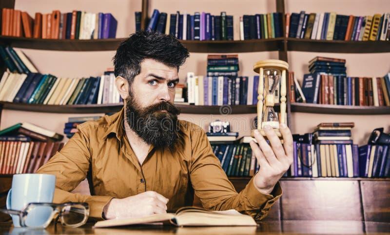 Bibliotheek en bibliothecaris De mens op nadenkend gezicht houdt zandloper terwijl het bestuderen, boekenrekken op achtergrond Le royalty-vrije stock afbeelding