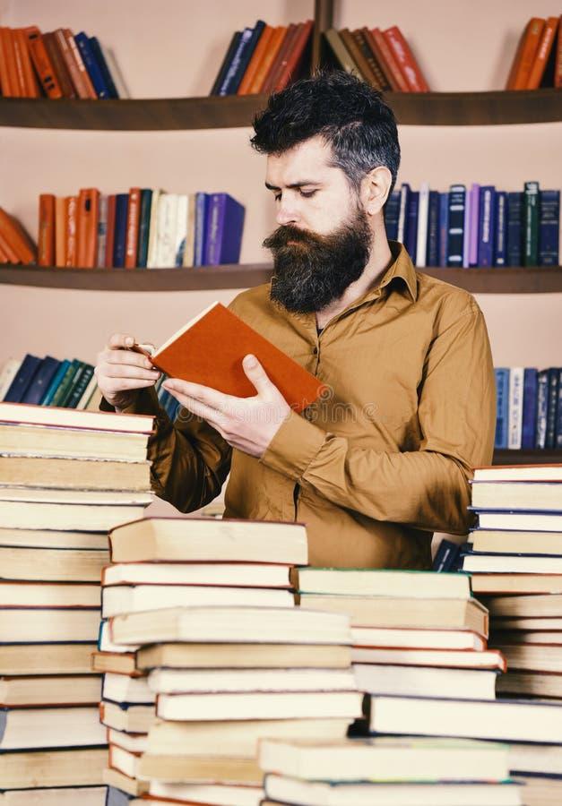 Bibliotheek en bibliothecaris Mens op het bezige nadenkende boek van de gezichtslezing, boekenrekken op achtergrond Leraar of stu royalty-vrije stock fotografie