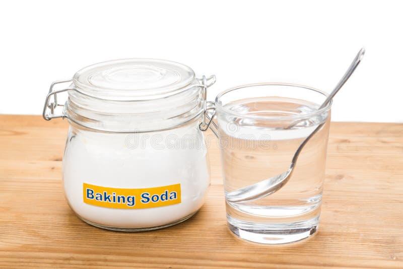 Bicarbonate de soude en pot, cuillerée et verre de l'eau pour HOL multiple photographie stock libre de droits