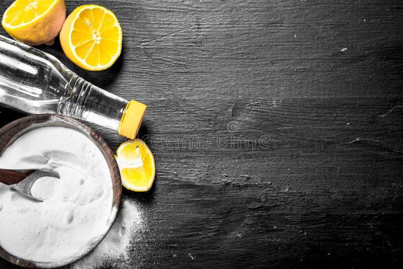 Bicarbonato de sódio em uma bacia com fatias do vinagre e do limão imagens de stock
