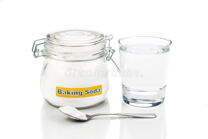 Bicarbonato di sodio in barattolo, cucchiaiata e bicchiere d'acqua per la HOL multipla immagini stock