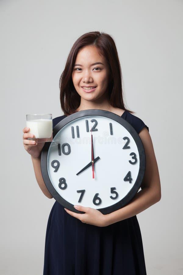 Bicchiere asiatico sano della donna dell'orologio della tenuta del latte immagini stock libere da diritti