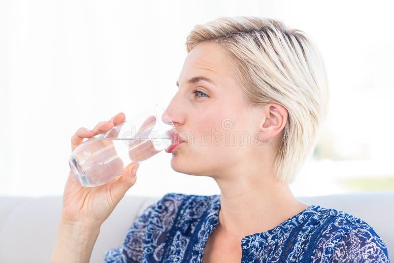 Bicchiere biondo grazioso della donna di acqua fotografie stock libere da diritti