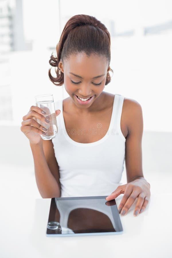 Bicchiere d'acqua di tenuta di modello sportivo felice facendo uso del pc della compressa immagine stock libera da diritti