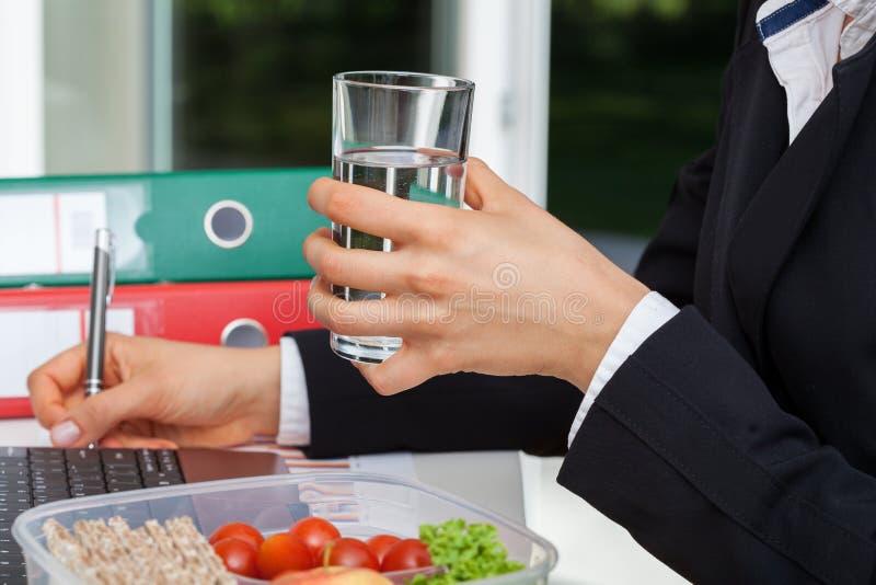 Bicchiere d'acqua durante il lavoro fotografie stock