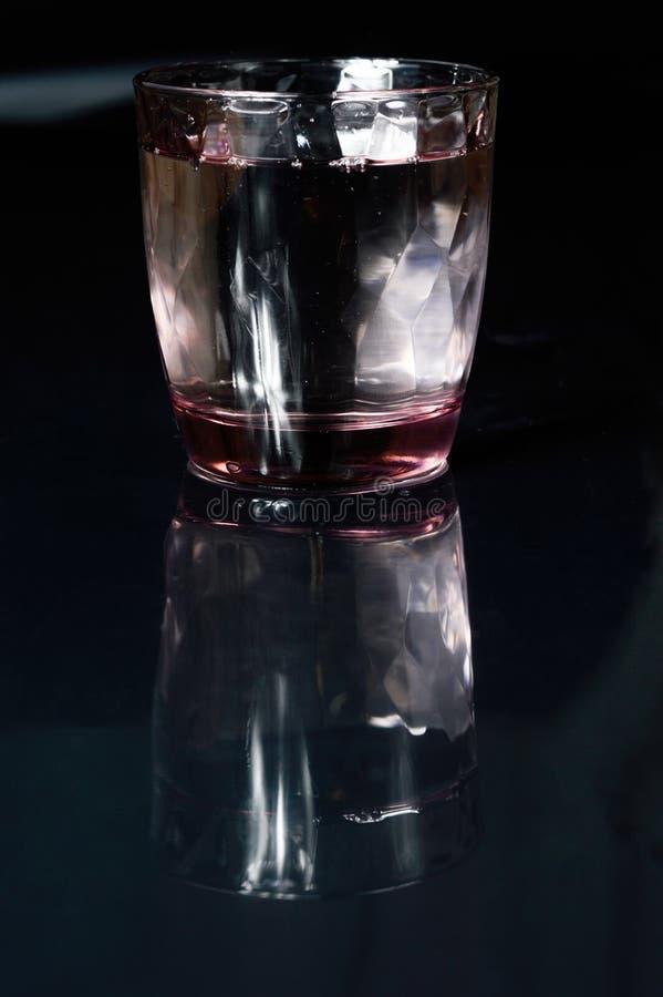 Bicchiere d'acqua e refleciton fotografia stock