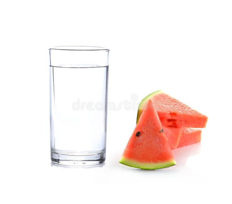 Bicchiere d'acqua ed anguria isolati su fondo bianco immagini stock