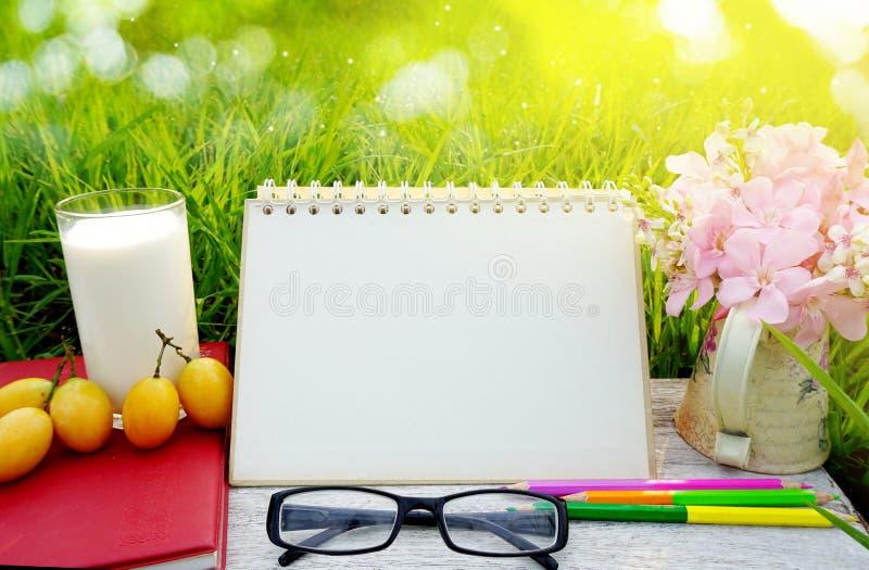 Bicchiere di latte, calendario della pagina in bianco, frutta gialla, occhiali da sole, matite e fiore rosa sulla tavola di legno immagini stock