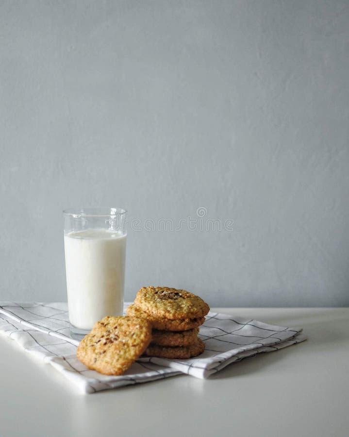 Bicchiere di latte con i biscotti di farina d'avena dello zenzero del homemeade con l'asciugamano bianco su fondo grigio fotografie stock