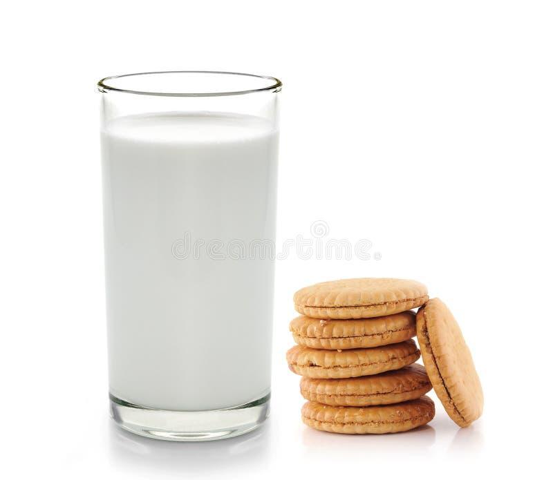 Bicchiere di latte e biscotti su bianco fotografie stock