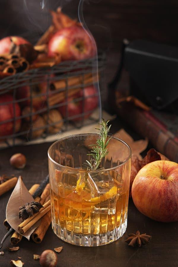 Bicchiere di whiskey alcolico con ramificazione di rosmarino con fumo e mele, bastoni di cannella Concetto di autunno magico immagine stock