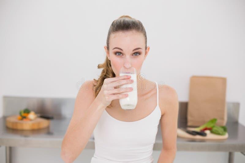 Bicchiere serio della giovane donna di latte fotografie stock