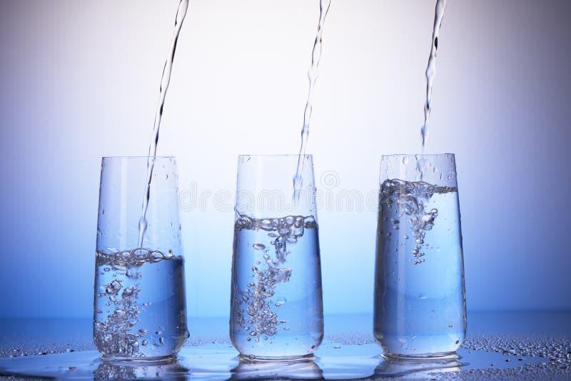 Bicchieri con la riflessione nelle gocce Versamento dell'acqua immagine stock