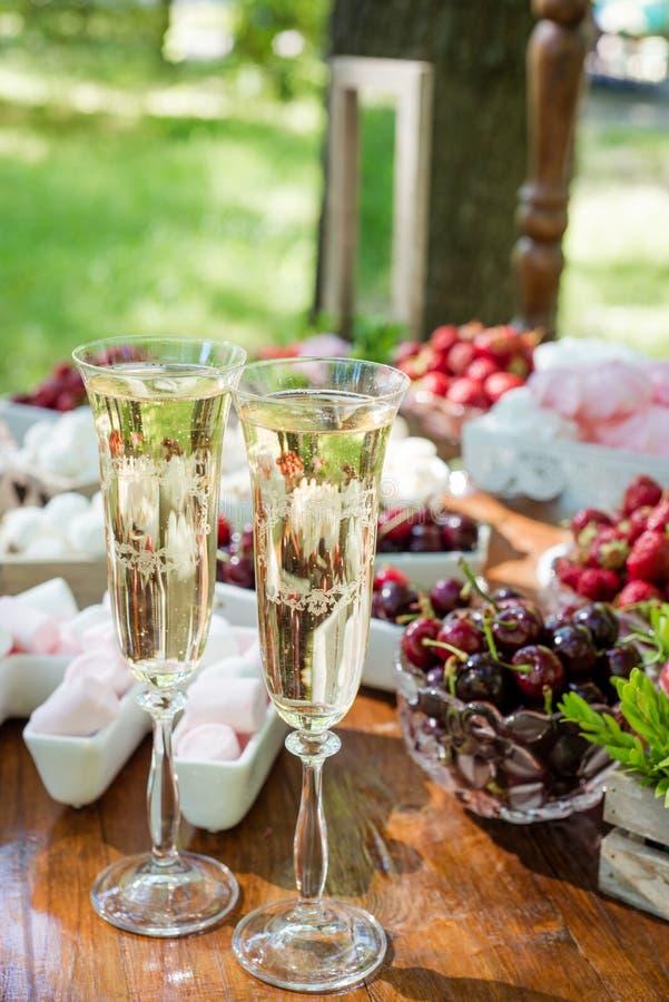 Bicchieri di vino festivi della regolazione della tavola con champagne, frutta e le caramelle gommosa e molle immagine stock