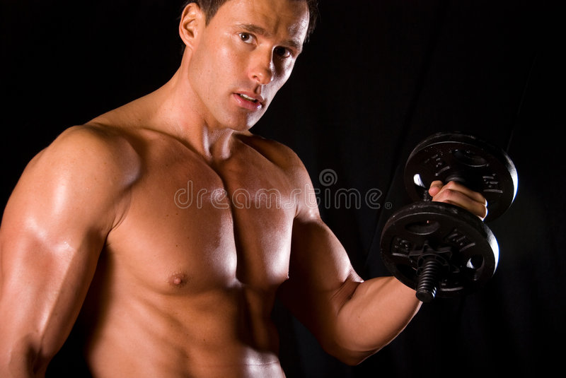 Bicep curl. Muscular man doing a bicep curl. He is looking at the camera. Black background royalty free stock images