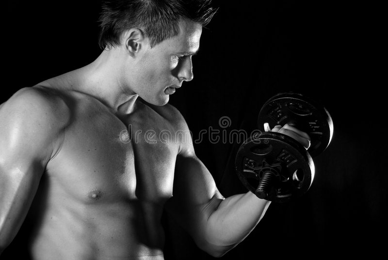 Bicep curl. Muscular man doing a bicep curl. He is looking at the weight. Black background royalty free stock photos