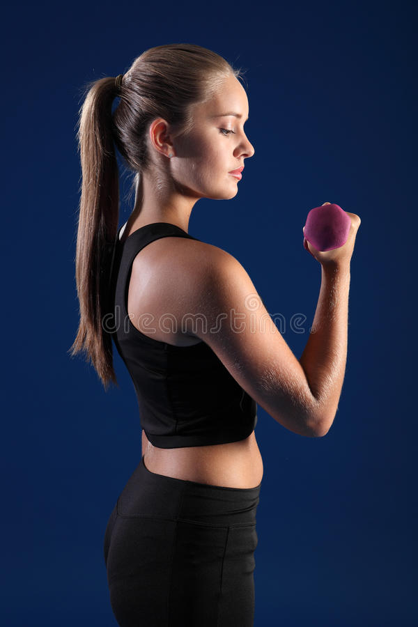 Bicep curl by beautiful young fitness woman stock photo