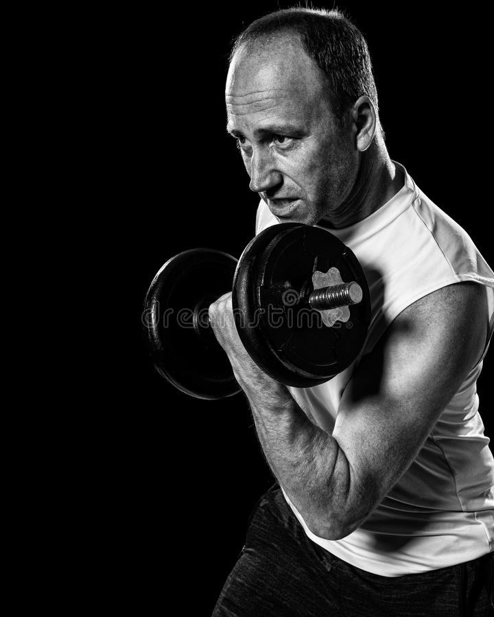 Bicep Curl. Exercise with dumbbell. Studio shot over black royalty free stock photo