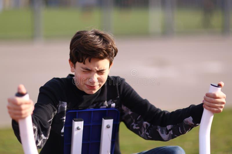 Bicepens för arm för tonåringpojkeutbildning i utomhus- idrottshall i stad parkerar slut upp fotoet royaltyfri fotografi