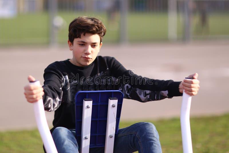 Bicepens för arm för tonåringpojkeutbildning i utomhus- idrottshall i stad parkerar slut upp fotoet royaltyfria foton