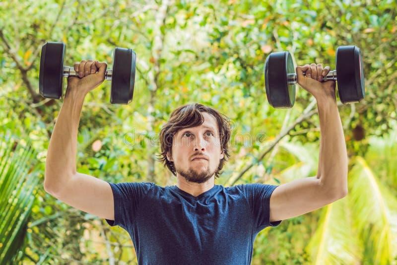 Bicepkrullning - armar för mannen för viktutbildningskondition som krullar utvändiga utarbetande lyfter hantlar som gör biceps Ma fotografering för bildbyråer