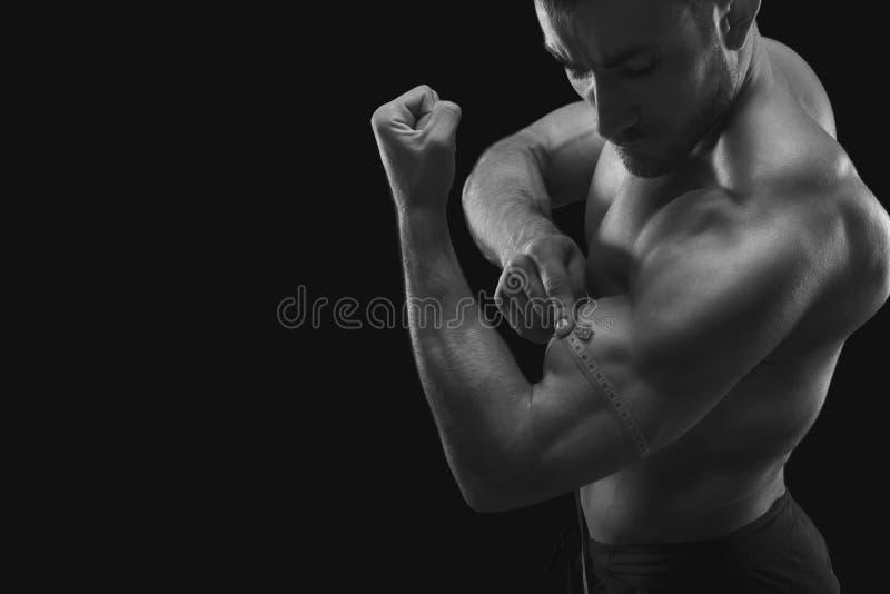 Biceps de mesure d'homme musculaire fort image libre de droits