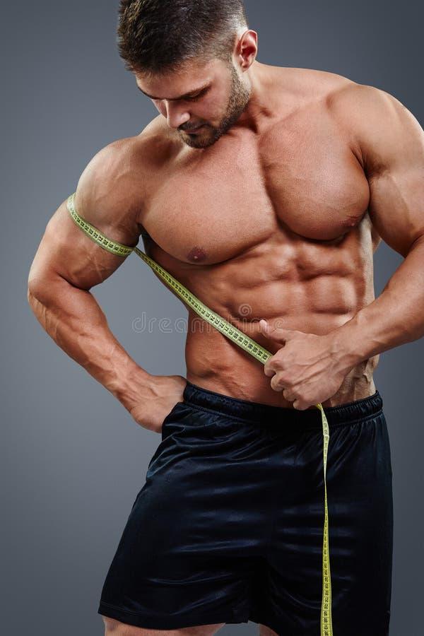 Biceps de mesure de Bodybuilder avec le ruban métrique photographie stock libre de droits