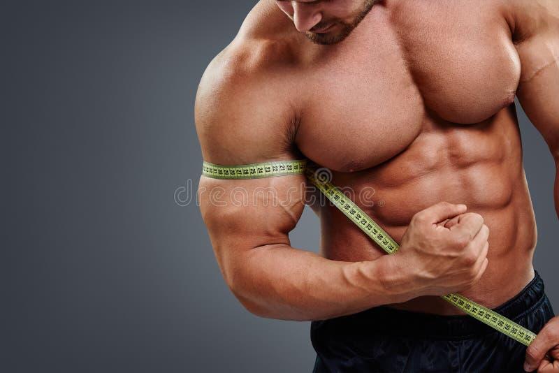 Biceps de mesure de Bodybuilder avec le ruban métrique images libres de droits