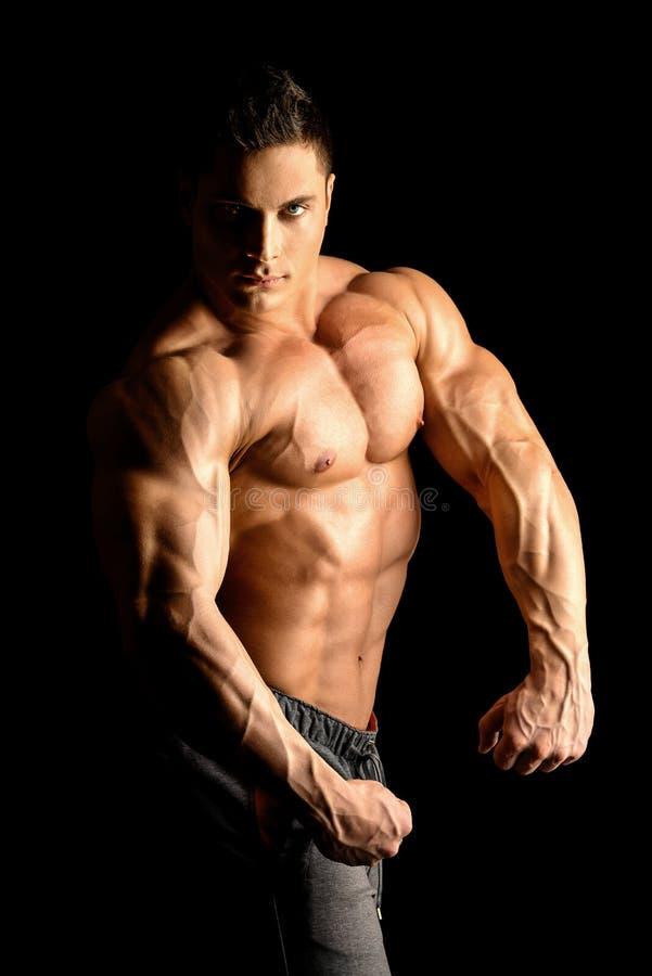 Biceps. Handsome muscular bodybuilder posing over black background royalty free stock image
