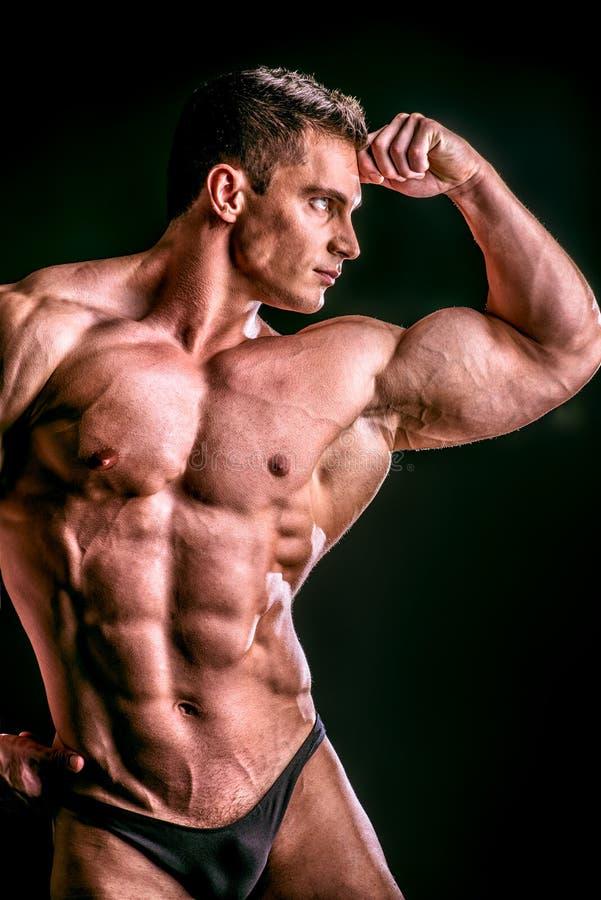 Biceps man. Handsome muscular bodybuilder posing over black background stock photo