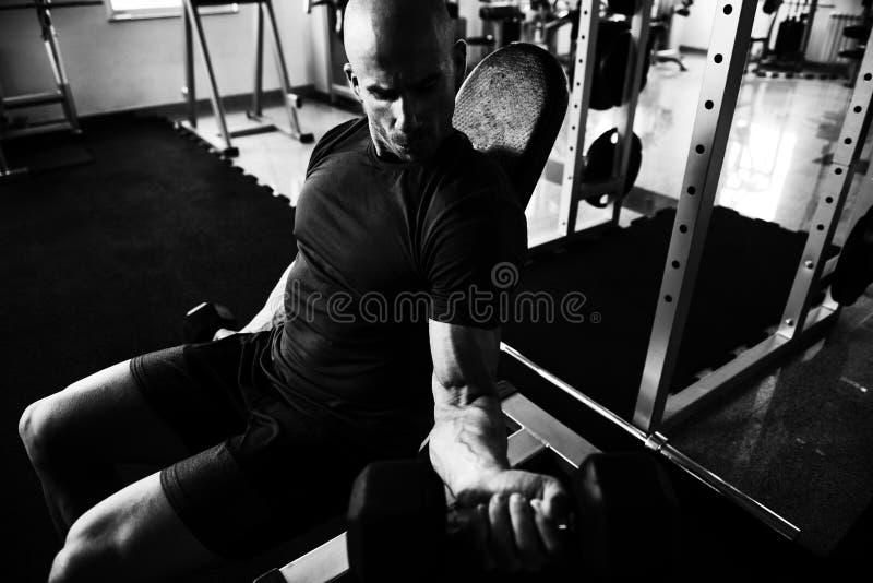Bicepsenoefening met Domoren in een Gymnastiek royalty-vrije stock foto's