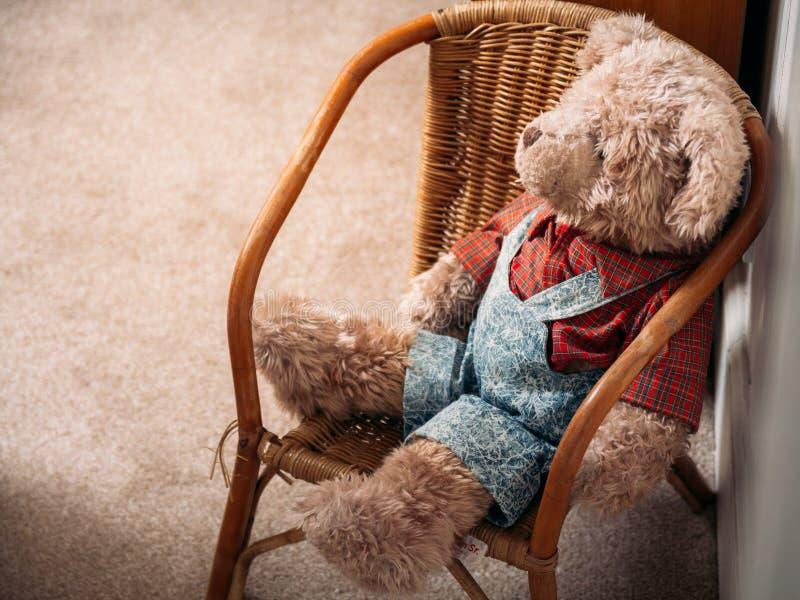 Bicho de pelúcia marrom macio do urso de peluche que senta-se em uma cadeira de vime d imagem de stock