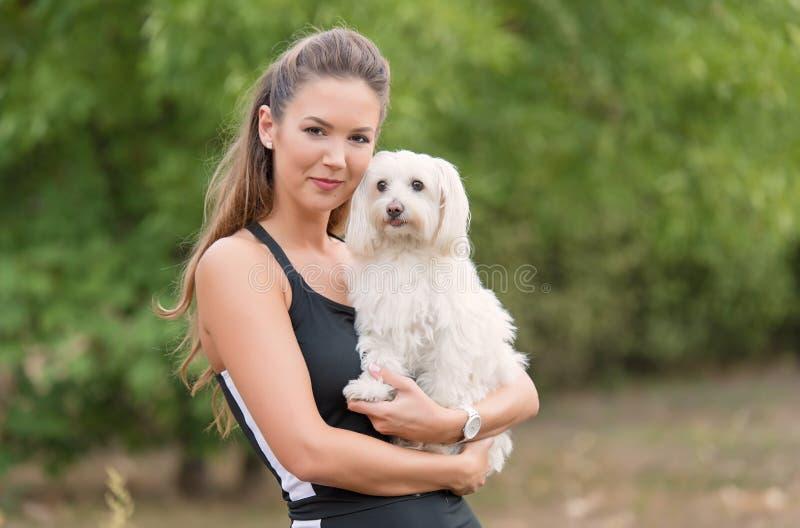 Bichon Bolognese pies z piękną kobietą w parku obraz stock