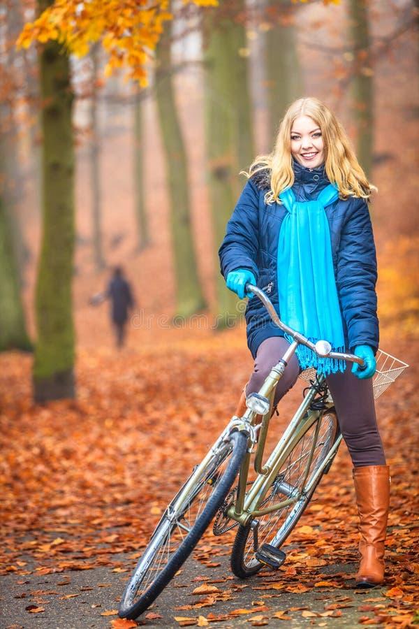Bici activa feliz del montar a caballo de la mujer en parque del otoño fotografía de archivo