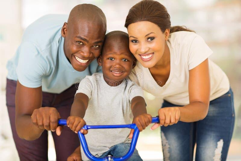 Bici africana del hijo de la pareja fotografía de archivo libre de regalías