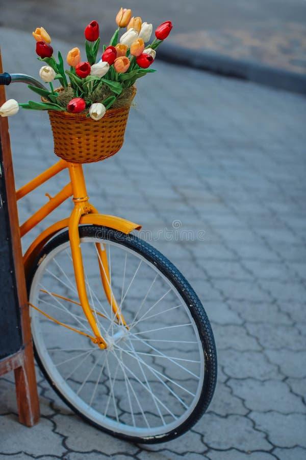 Bici anaranjada brillante con la cesta de flores fotografía de archivo